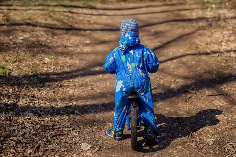Vista da dietro ad un piccolo bambino in una tuta blu pronta a dare dei calci a fuori sulla sua bici blu dell'equilibrio in prima fotografie stock