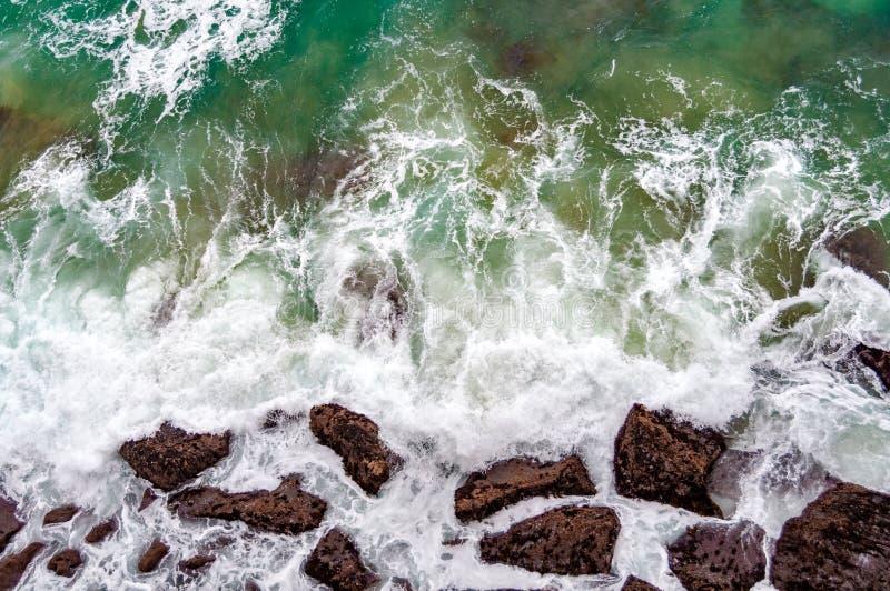 Vista da direttamente sopra sull'onda e sulle rocce del mare immagine stock