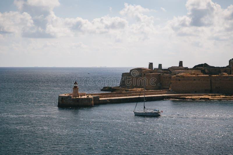 Vista da entrada de porto grande e do quebra-mar do leste medieval velho de Ricasoli com farol vermelho e do forte Ricasoli visto foto de stock royalty free