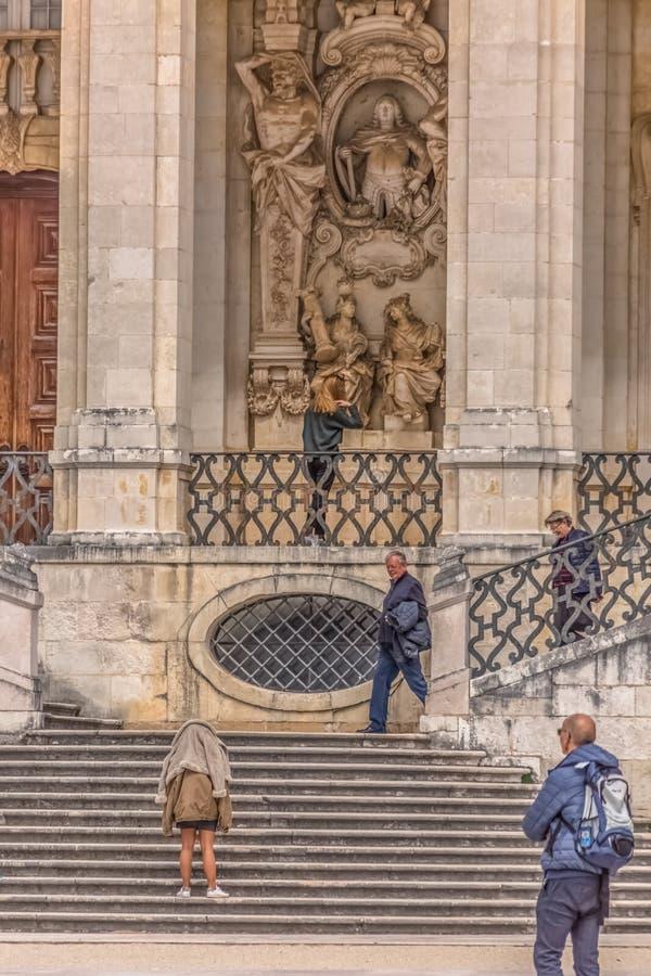 Vista da escadaria na universidade da lei em Coimbra, com os turistas a visitar Construção clássica com ornamento e esculturas, fotografia de stock royalty free