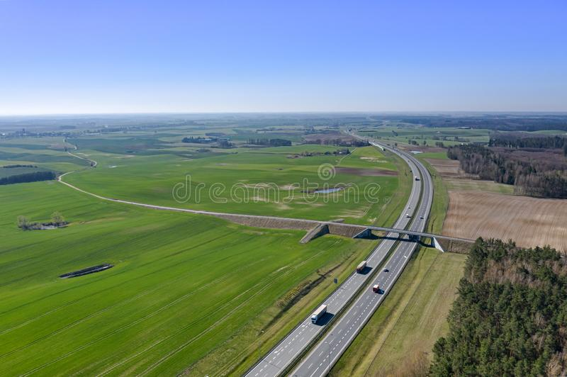 Vista da estrada com os carros sobre o fundo de campos e de florestas verdes imagem de stock royalty free