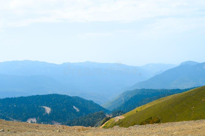 Vista da estrada de terra às montanhas enevoadas e ao monte fotografia de stock