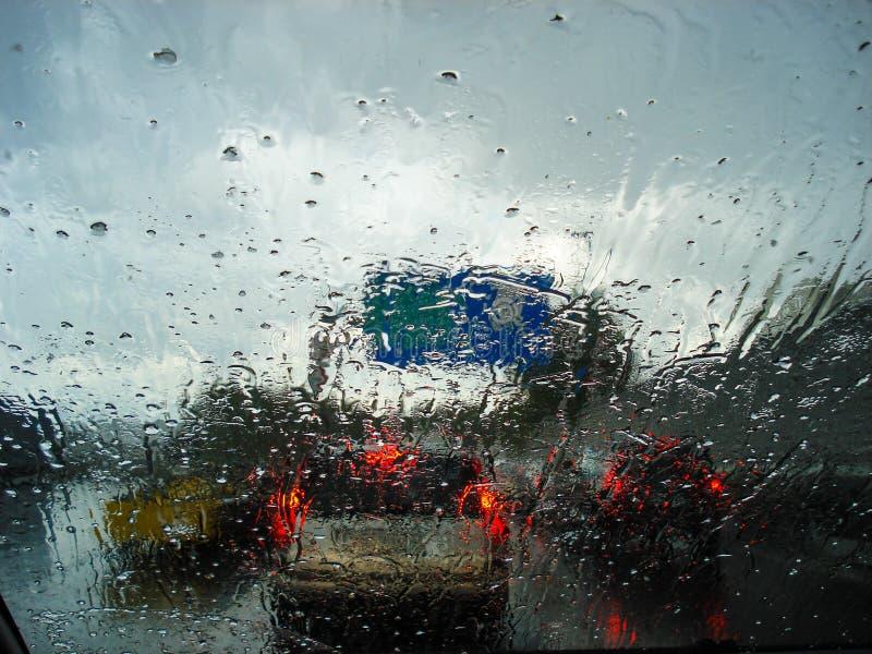 Vista da estrada e engarrafamentos em um dia chuvoso do interior de um carro com o vidro molhado do carro foto de stock