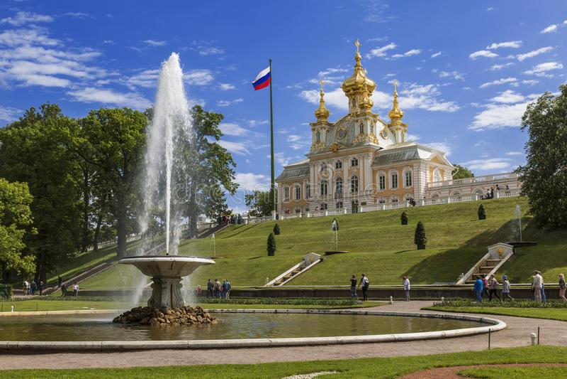 Vista da fonte da bacia francesa e da igreja do palácio de Peter e de Paul no parque mais baixo de Peterhof, St Petersburg, imagem de stock