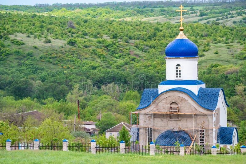 Vista da igreja ortodoxa pequena com as abóbadas azuis no reparo em Rússia fotos de stock
