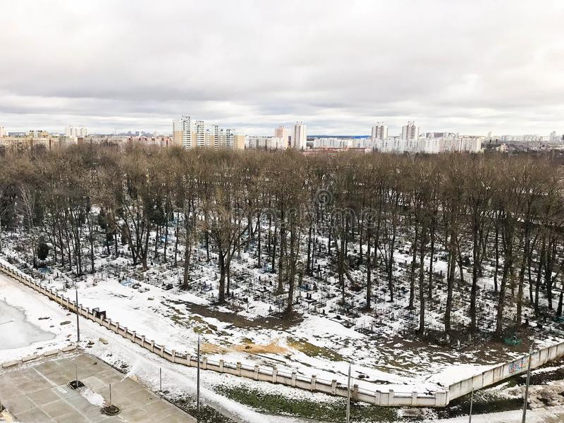 A vista da janela do cemitério velho da cidade no parque de uma altura com árvores e casas no inverno imagens de stock