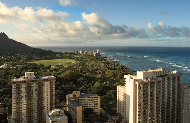 A vista da janela do hotel sobre a cidade de Havaí, de suas ruas, de hotéis, de ondas de oceano e de ressaca em um céu nebuloso d foto de stock