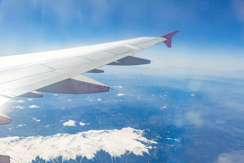 Vista da janela do plano que voa sobre as montanhas imagens de stock