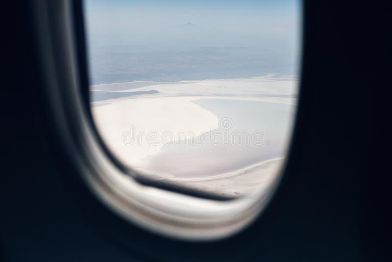 Vista da janela dos aviões nas paisagens abaixo, montanhas, lagos, florestas, mares Janela dos avi?es imagem de stock
