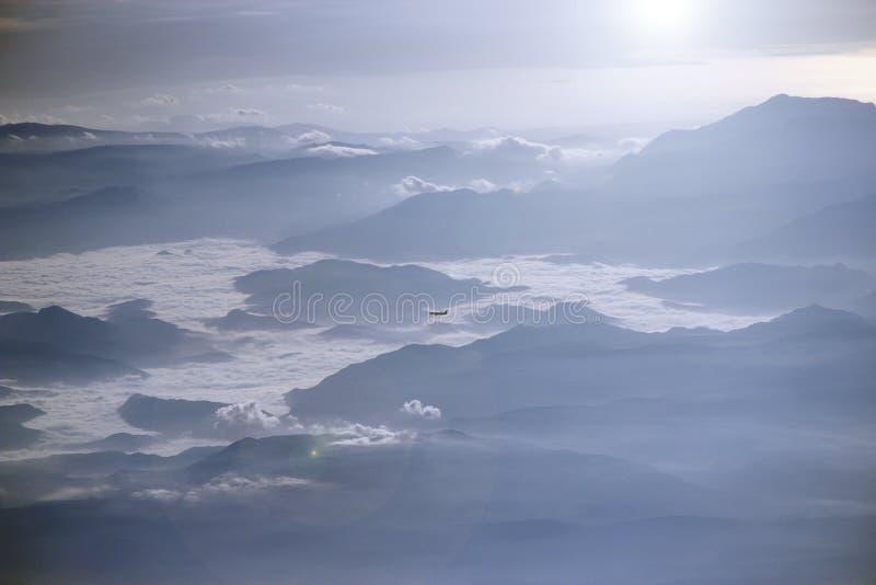 Vista da janela plana a um outro voo plano sobre nuvens e montanhas imagens de stock royalty free