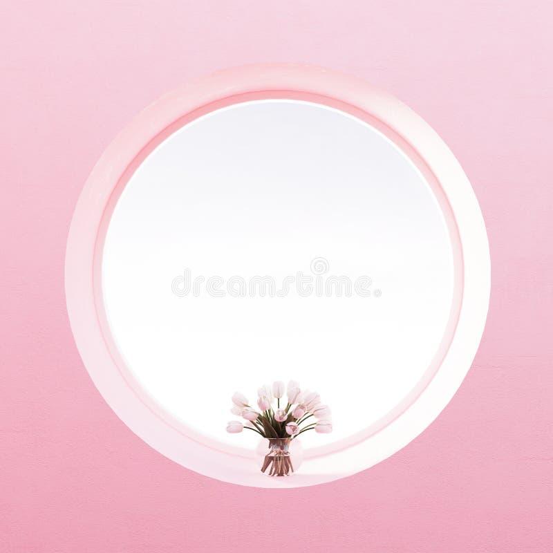Vista da janela redonda, flores, parede pastel do rosa da pérola fotos de stock royalty free