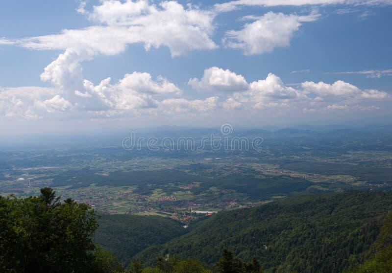 Vista da Medvednica, montagna di Sljeme a Zagabria, Croazia Abbellisca la foto con cielo blu, le nuvole bianche e gli alberi verd fotografie stock