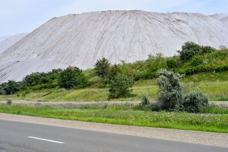Vista da mina de sal e de um monte artificial com grama verde no primeiro plano foto de stock