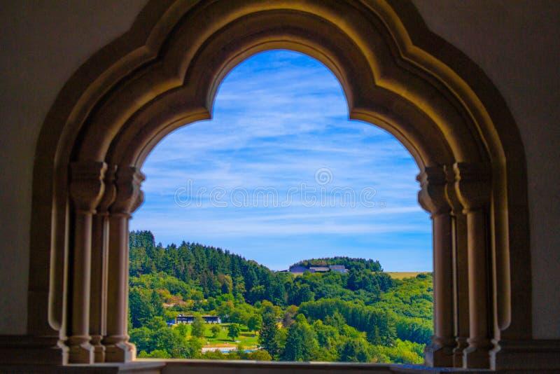 Vista da montanha e da floresta em Vianden, Luxemburgo, de um arco dentro do castelo de Vianden fotografia de stock