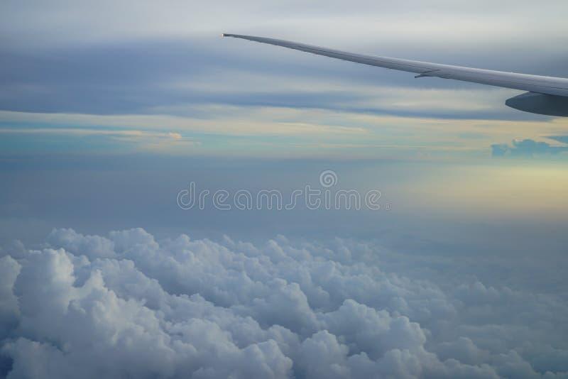 Vista da nuvem branca abstrata macia e do céu azul com asa do avião e fundo claro do nascer do sol da janela do avião imagem de stock royalty free