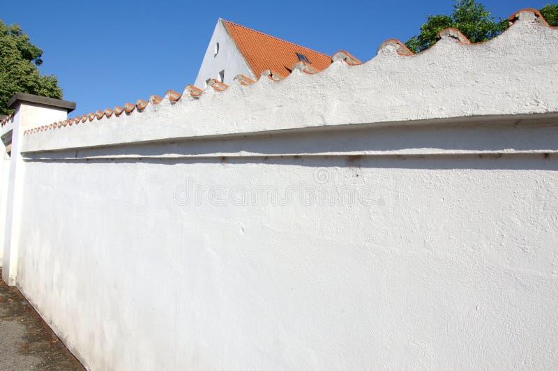 Vista da parede de pedra branca real velha com a casa circunvizinha da telha de telhado imagens de stock