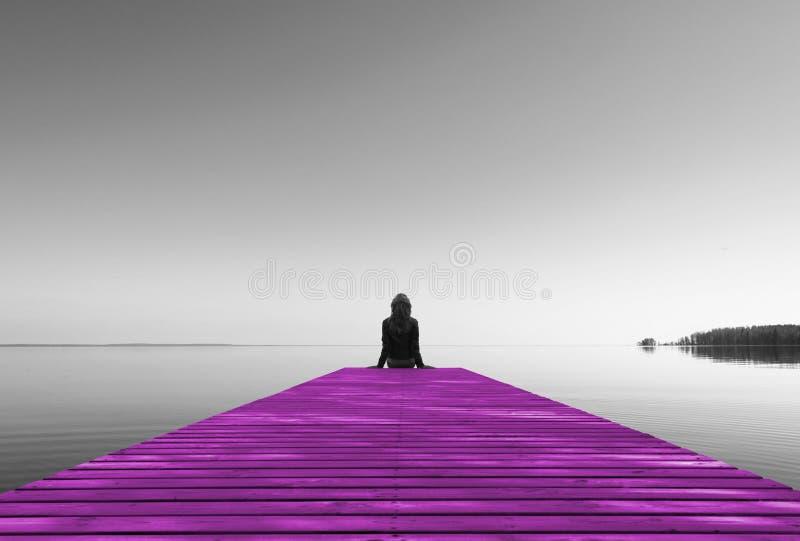 Vista da parte de trás da menina bonita e saudável que senta-se no cais de madeira cor-de-rosa Férias, recurso e conceito de viag fotografia de stock
