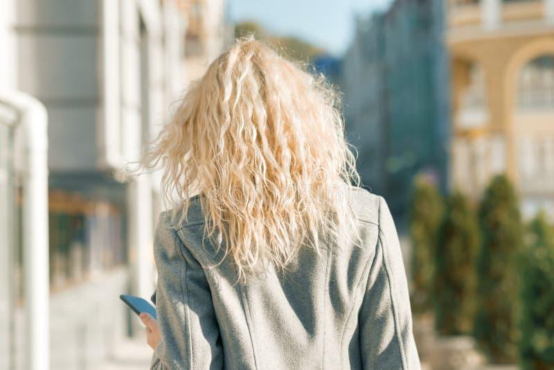 Vista da parte de trás da mulher loura nova que anda ao longo da rua da cidade, dia ensolarado do outono imagem de stock