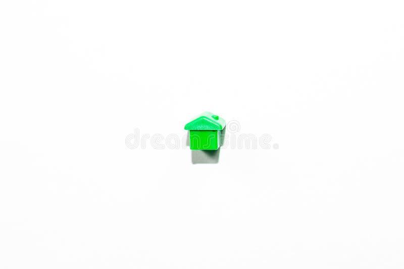 Vista da parte superior da casa diminuta plástica no verde como uma parte do jogo do monopólio em um fundo branco fotografia de stock