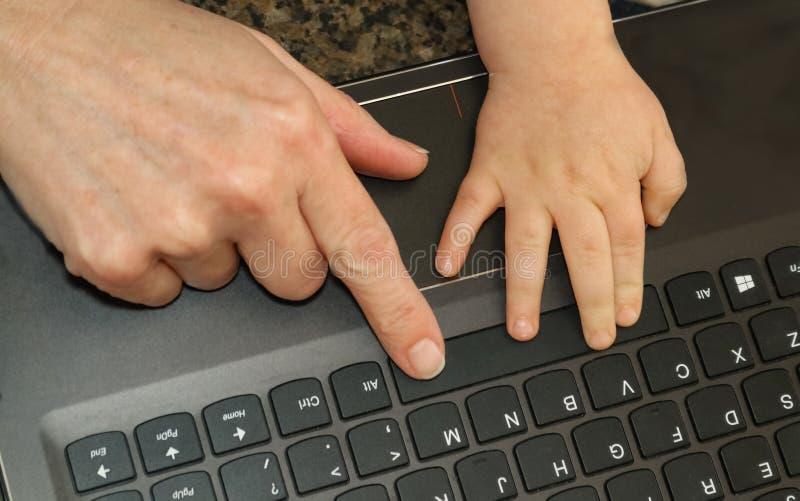 Vista da parte superior do dedo de uma mulher e de uma mão dos childs em um portátil k imagens de stock