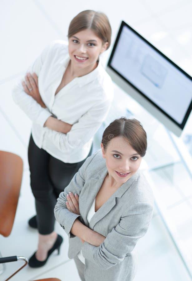 Vista da parte superior duas mulheres de negócio bem sucedidas que estão no escritório e que olham a câmera fotos de stock