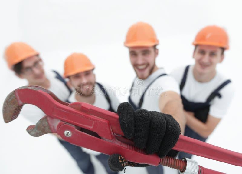 Vista da parte superior grupo de construtores que mostram uma chave do gás imagens de stock
