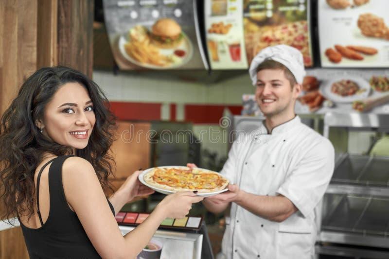 Vista da parte traseira da mulher alegre que compra a pizza saboroso no café imagens de stock royalty free