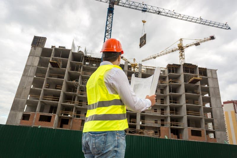 Vista da parte traseira no inspetor que olha a construção sob o constructi imagens de stock