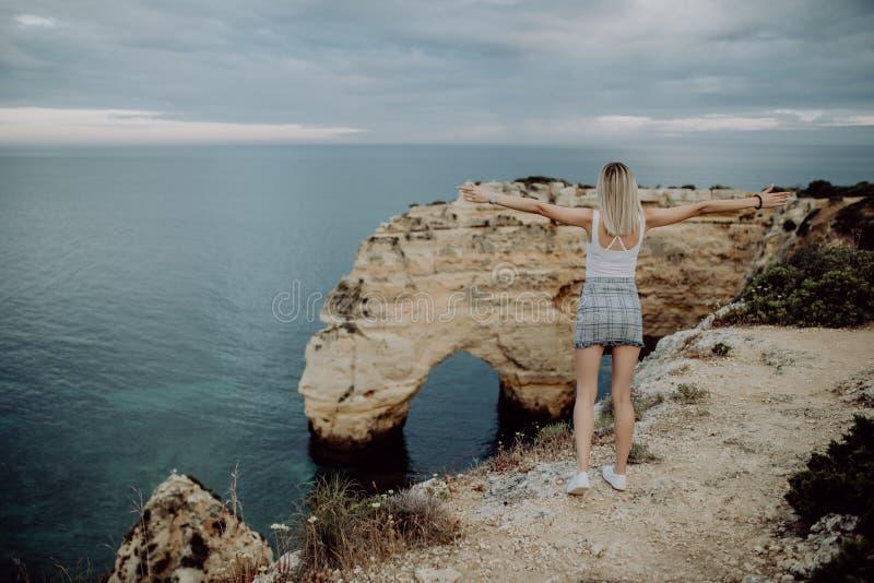 Vista da parte traseira Um turista da jovem mulher aprecia as vistas bonitas do Oceano Atlântico e a paisagem fora da costa no po imagens de stock royalty free