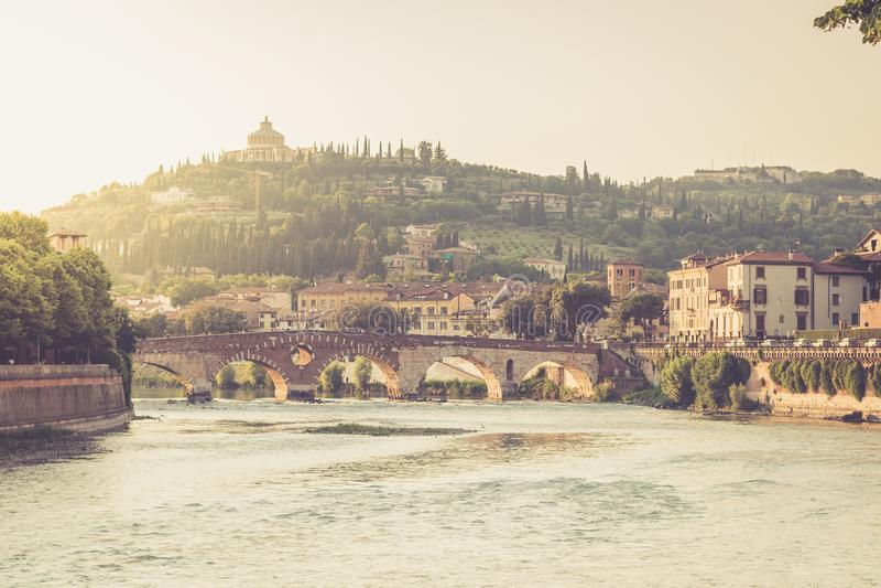 Vista da ponte de Ponte Pietra no rio de Adige iluminado pelo por do sol em Verona foto de stock
