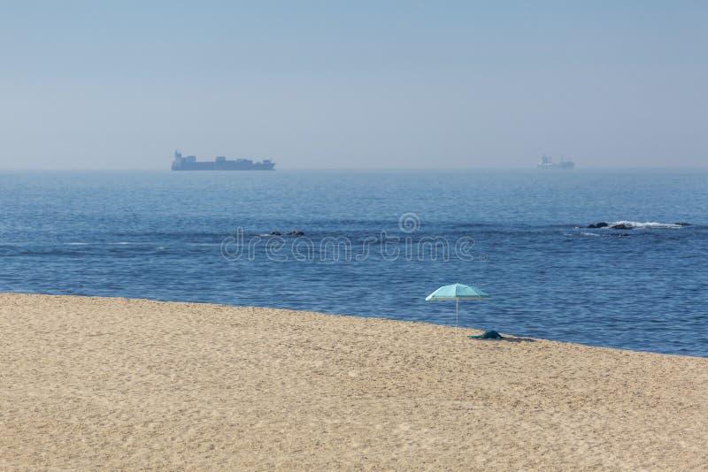 Vista da praia com areia limpa, parasol da praia, na praia, com toalha, mar com onda, barco e navio, céu com gaivota como imagens de stock royalty free