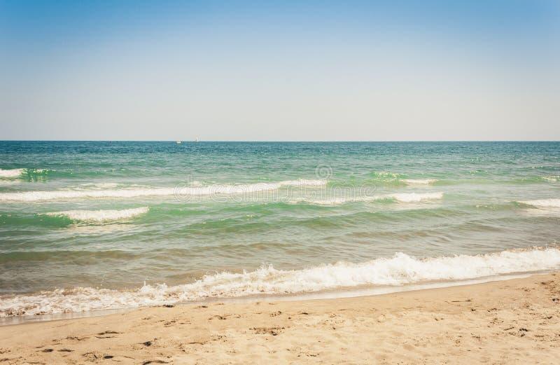 A vista da praia de Catania, Sicília, Itália, Lido Cled com o verde windsurf placa no mar foto de stock
