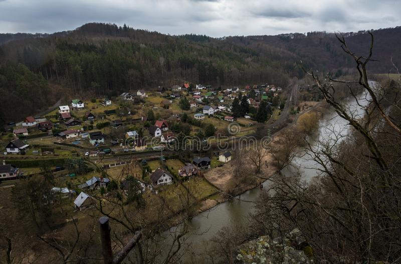 Vista da rocha ao rio que corre através do vale com casas imagem de stock royalty free
