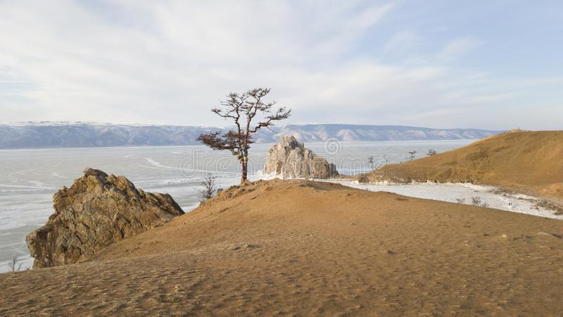 Vista da rocha de Shamanka e do cabo Burkhan na ilha de Olkhon em Sibéria Costa Baikal-arenosa do inverno e gelo bonito no lago foto de stock