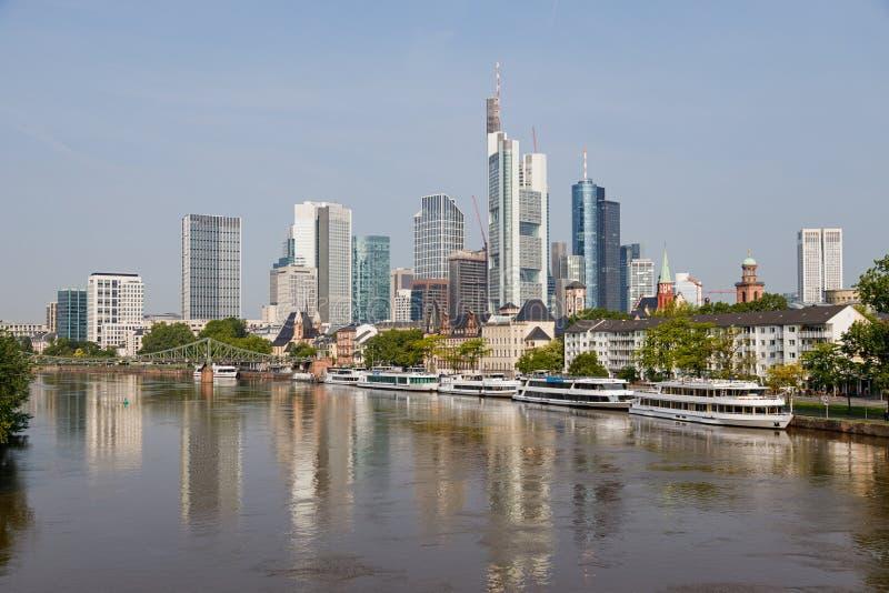 Vista da skyline famosa de Francoforte e do distrito bancário com o cano principal de rio no primeiro plano e contra um céu azul imagem de stock royalty free