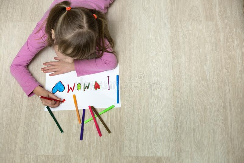 Vista da sopra del disegno sveglio della ragazza del bambino con i pastelli variopinti amo la mamma su Libro Bianco Educazione ar immagini stock libere da diritti