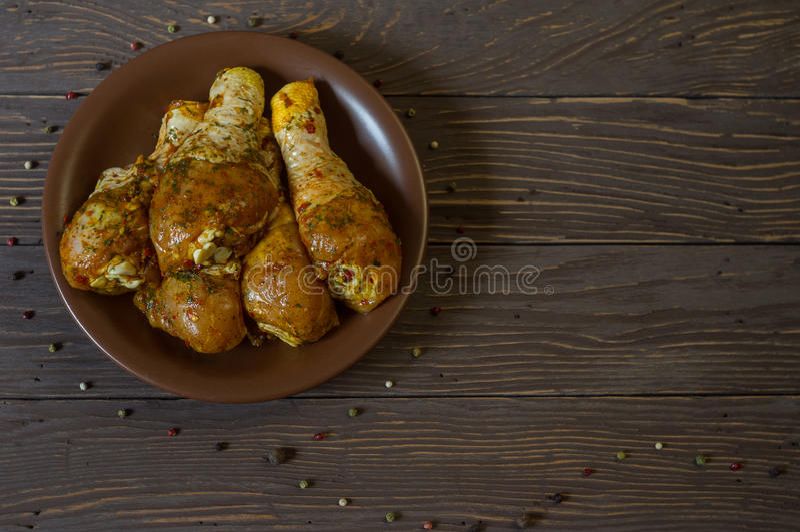 Vista da sopra Le coscie di pollo crude ricoperte di spezie si trovano su un vassoio Fondo Colore del pepe immagini stock