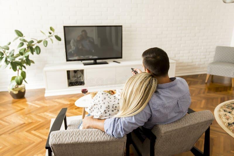 Vista da televisão de observação dos pares na sala de visitas fotos de stock royalty free
