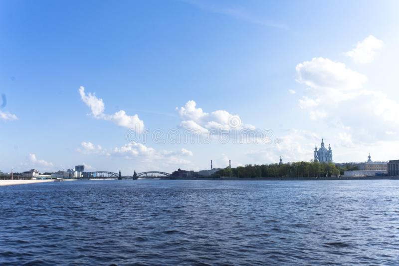 Vista da terraplenagem de Sverdlovsk, St Petersburg Rio Neva na mola Catedral de Smolny na distância imagem de stock royalty free