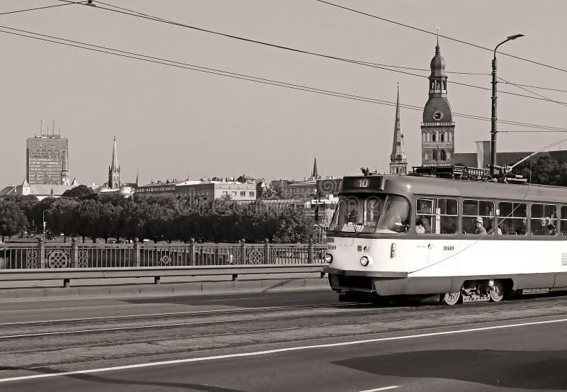 Vista da torre de sino velha da cidade da catedral de Riga e do bonde velho na ponte de pedra, Riga, Letónia foto de stock