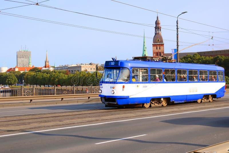 Vista da torre de sino velha da cidade da catedral de Riga e do bonde velho na ponte de pedra, Riga, Letónia fotos de stock royalty free