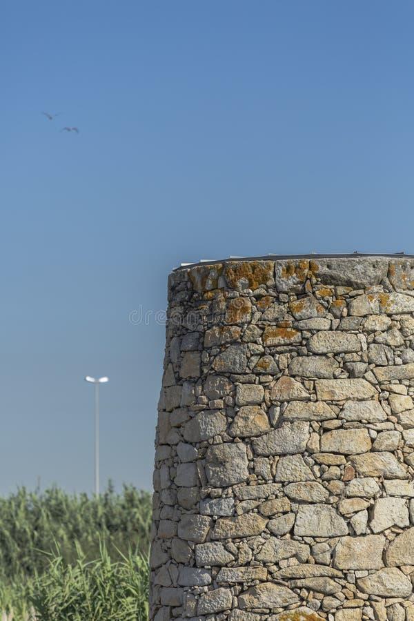 Vista da torre pequena em pedras detalhadas do granito, e fundo borrado com campos do bastão, pássaros no céu azul fotografia de stock