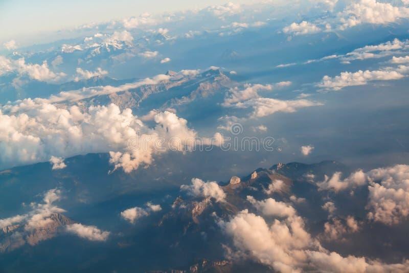 Vista da un aeroplano sulle montagne e sulle nuvole immagini stock