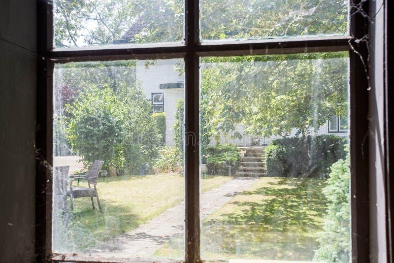 Vista da una costruzione abbandonata con una vecchia finestra sporca che esamina il giardino verde accogliente di eccedenza fotografia stock