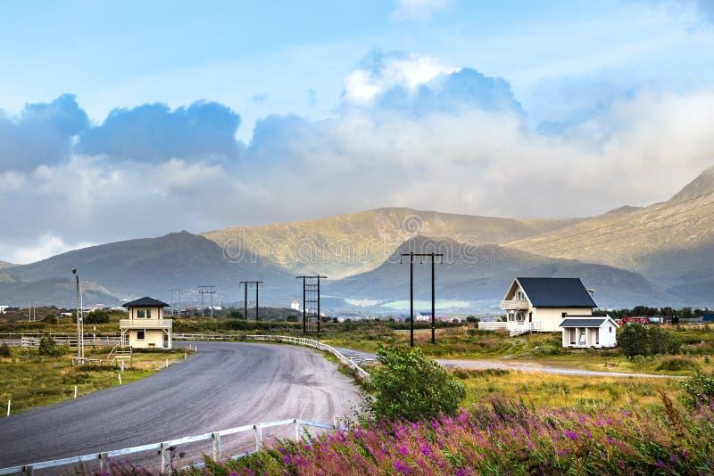 Vista da una strada con le montagne e le case di legno, Leknes, Norvegia immagine stock