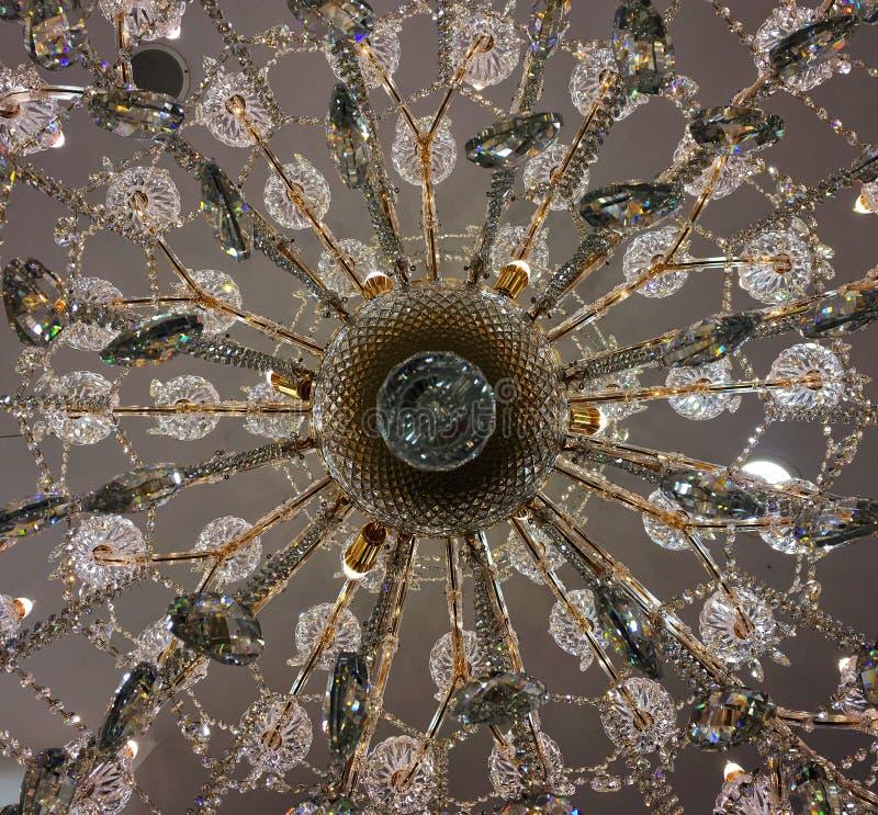 Vista dal basso al centro di caduta a cristallo della lampada del candeliere sul soffitto bianco fotografie stock