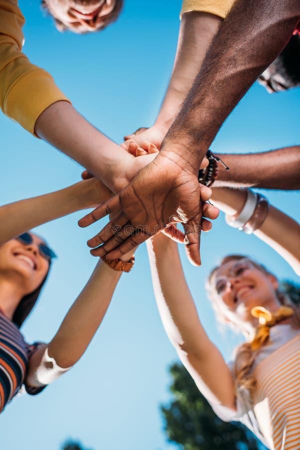 vista dal basso di giovani amici multirazziali che si tengono per mano insieme al cielo blu immagini stock