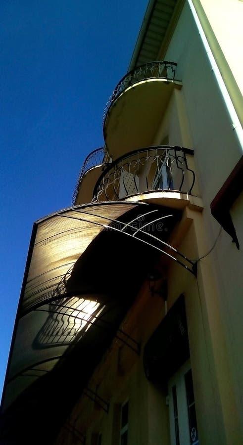 Vista dal basso di una costruzione luminosa con i balconi e di un baldacchino contro un cielo blu immagine stock