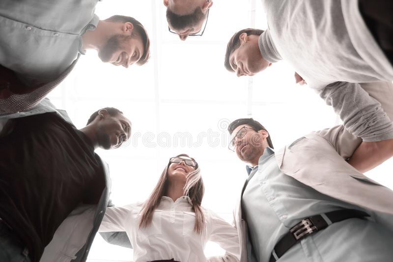 Vista dal basso il gruppo di affari sta insieme, formando un cerchio fotografia stock libera da diritti
