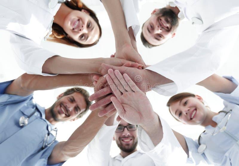 Vista dal basso un gruppo di medici al centro medico ha afferrato insieme le loro mani fotografie stock